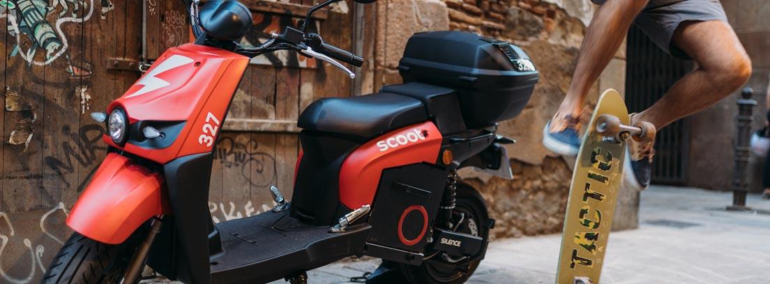 Moto de scoot aparcada junto a una skate.