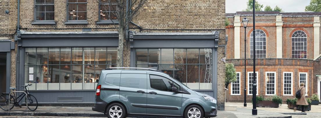 Ford Transit Courier azul estacionado frente a un edificio de ladrillo