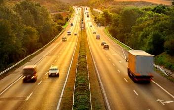 Autopista de peaje con vegetación frondosa a los lados