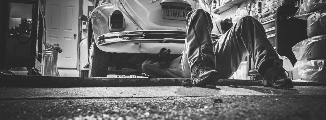 Mecánico mirando en la parte baja de un coche