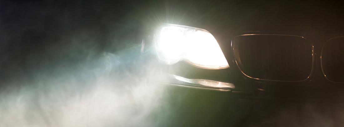 Faro encendido de un coche en la oscuridad