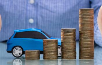 Maqueta de coche azul junto a columnas de monedas entre unas manos.