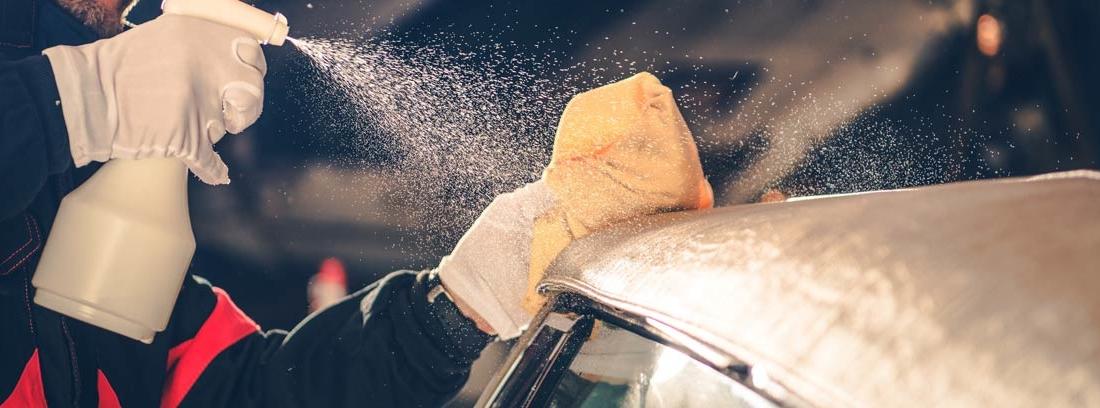 Persona aplicando spray sobre capota de coche