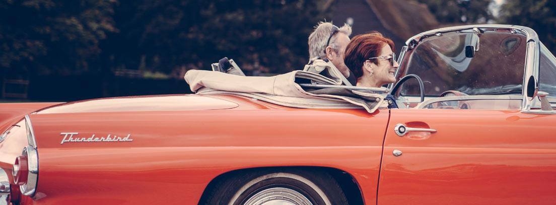 Coche clásico de color rojo con capota plegada con hombre y mujer dentro.