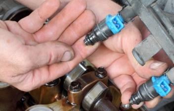 Manos tocando la fijación de un inyector de combustible en un motor de gasolina