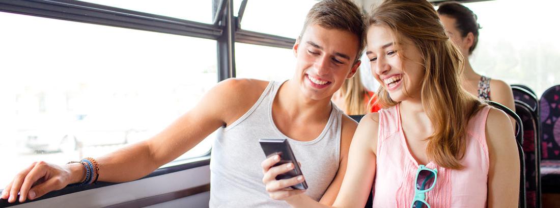 Hombre y mujer sonrientes mirando un móvil dentro de un autobús, el transporte público más usado en España