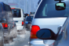 Varios coches en un atasco echando humo blanco por el tubo de escape