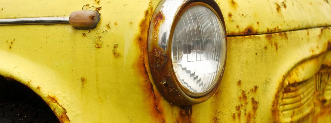 Primer plano del faro de un coche amarillo con la carrocería oxidada