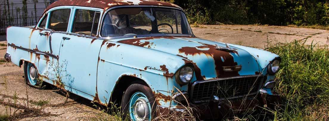 Coche azul con la carrocería con manchas de óxido