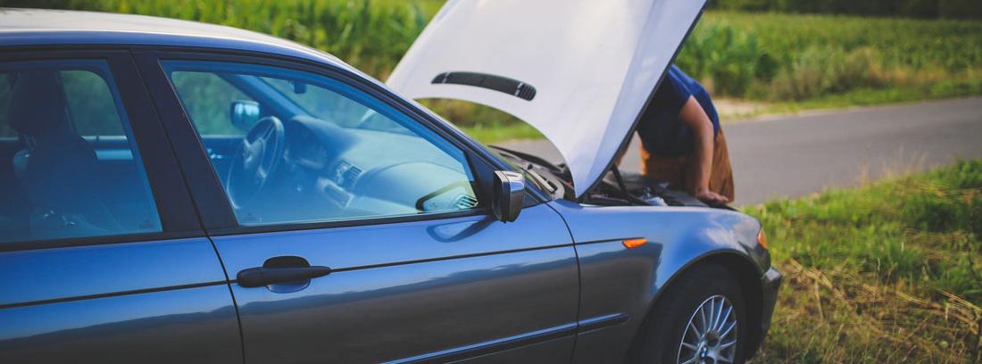 Coche parado con capó abierto y persona mirando motor