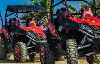 Fila de buggies rojos aparcados sobre arena