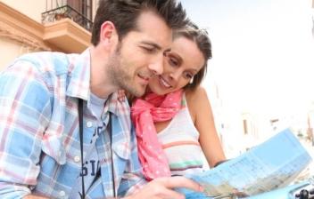 Mujer y hombre miran mapa sobre un ciclomotor azul