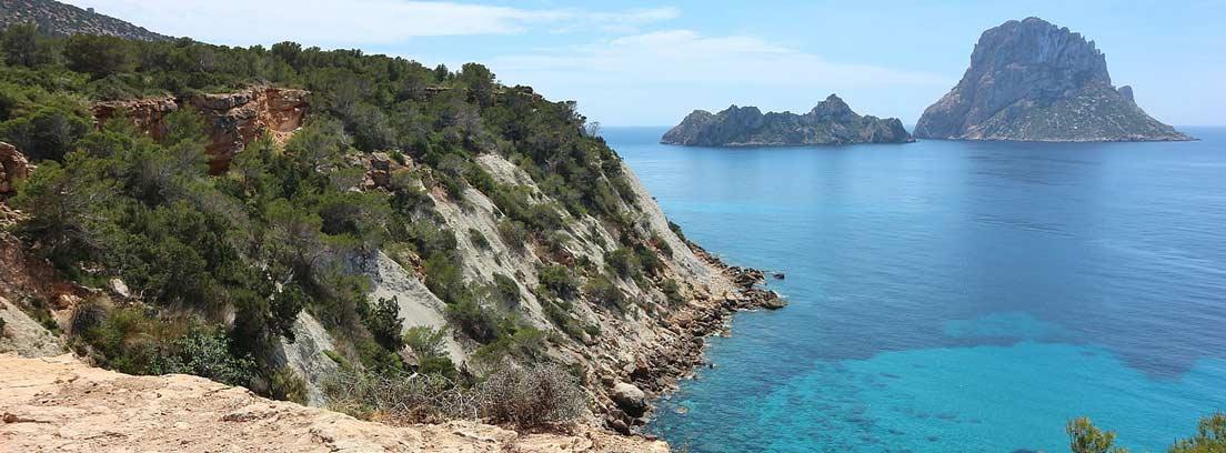Vista la isla de Es Vedra en Ibiza desde un pequeño acantilado.