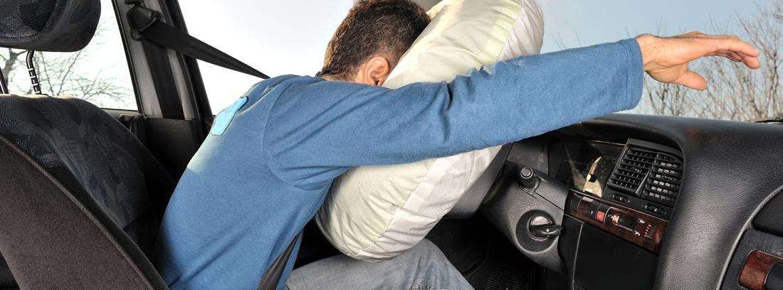 Hombre dentro de un coche con la cabeza apoyada en el airbag del volante