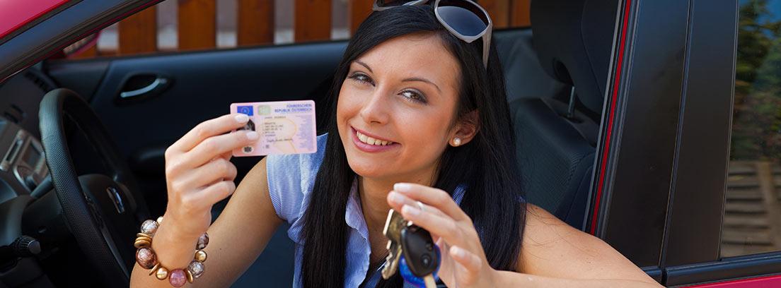 Mujer sonriente asomada por la ventanilla de un coche mostrando el duplicado de su carnet de conducir