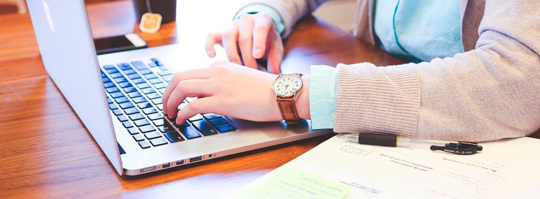 Vista parcial de unas manos de mujer sobre un ordenador