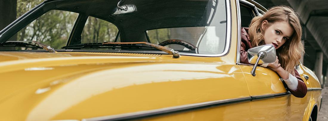 Mujer asomada por la ventanilla de un coche clásico