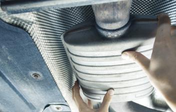 Hombre cambiando el tubo de escape del coche