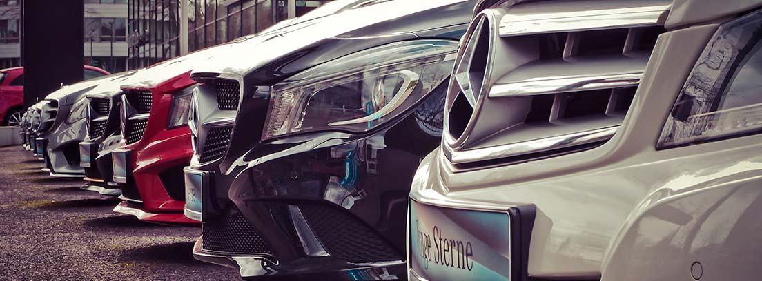 Diferentes coches aparcados en línea y visto desde la parte delantera