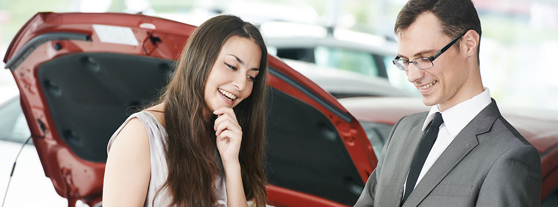 Mujer junto a hombre con carpeta y delante de un coche con capó abierto