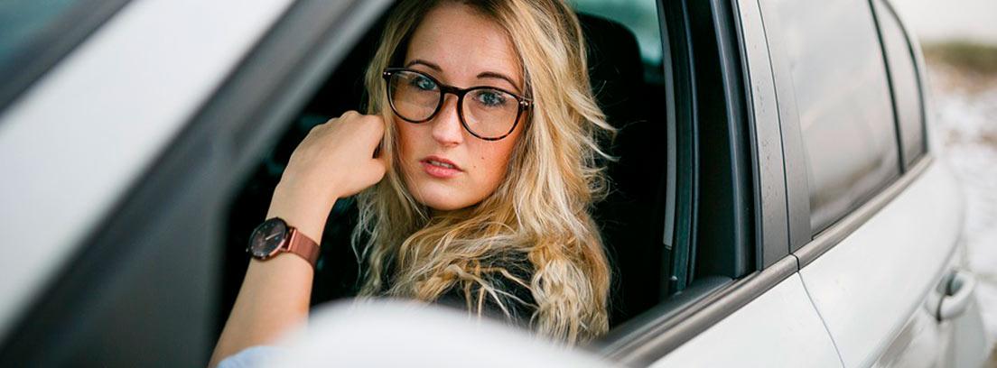 Chica joven mirando por la ventana de su coche