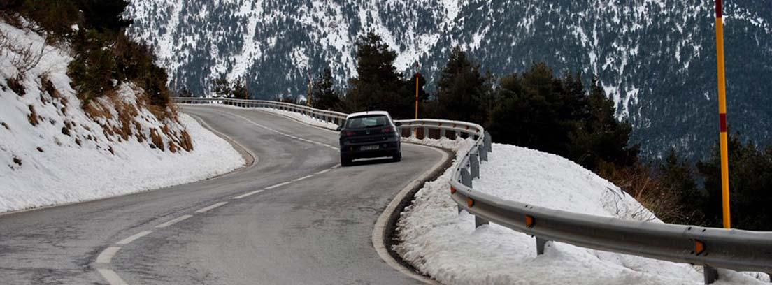 Coche circulando por carretera de puerto de montaña con nieve