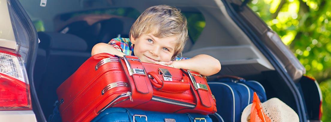 coche con exceso de equipaje y un niño sobre una maleta