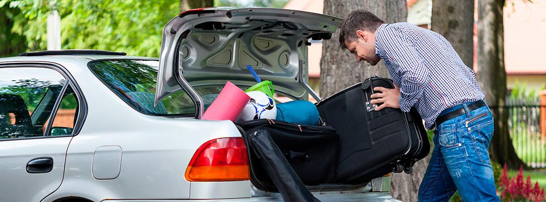 Hombre empuja maleta dentro de un maletero ya completo