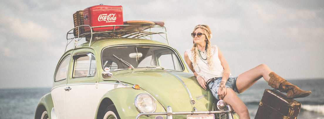 Mujer apoyada en el capó de un coche con baca y con maleta a su lado