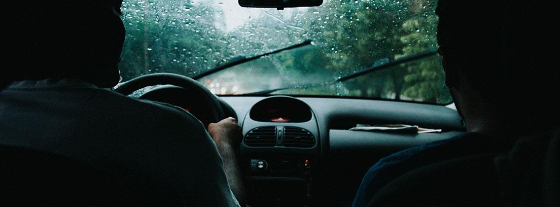 Interior de coche bajo la lluvia con una persona al volante y otra al lado