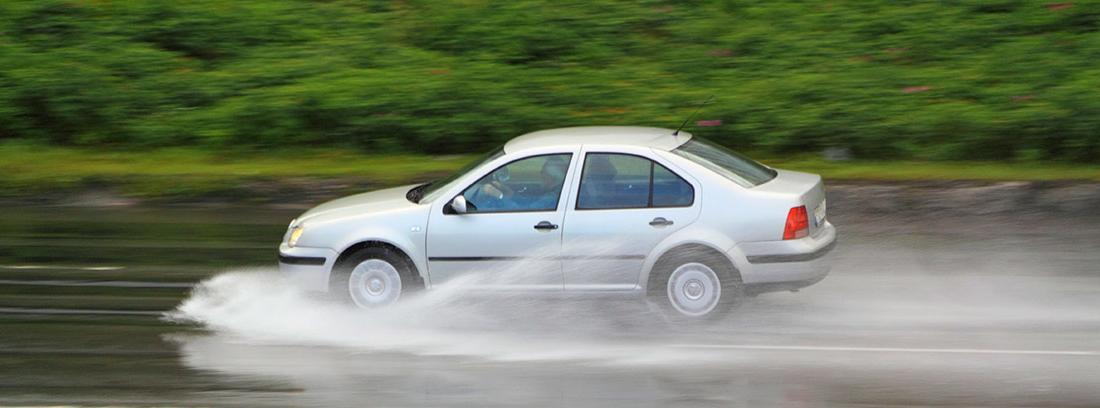 Coche circulando sobre agua y salpicando gran cantidad de agua a su alrededor