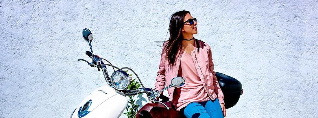 Mujer pensativa apoyada en una moto blanca