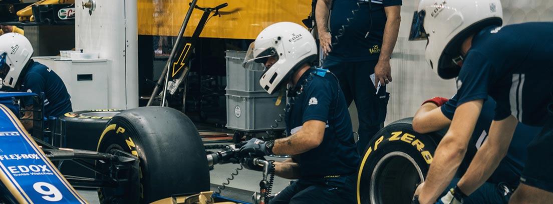 Mecánicos revisando ruedas y motor de un F1 en carrera