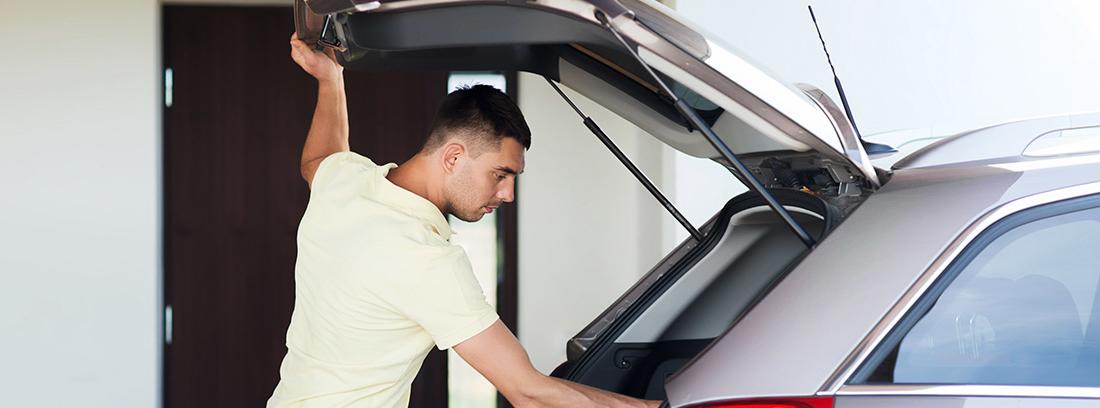 Hombre con una mano en el portón abierto del maletero de coche