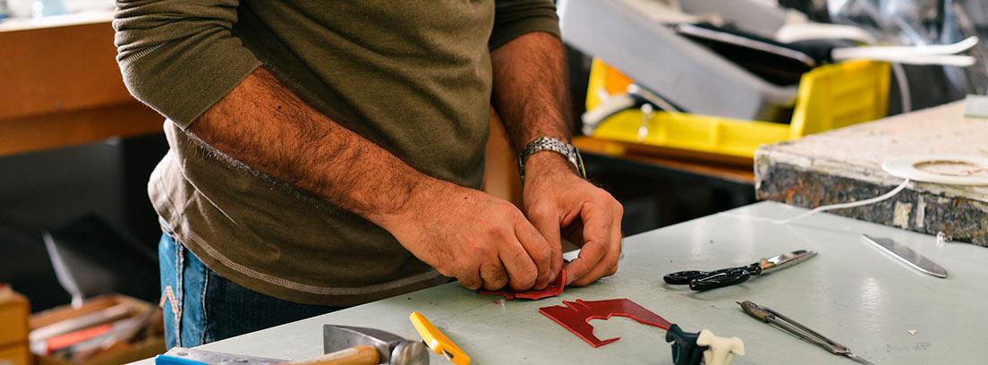 Mano de hombre manipulando piezas sobre mesa junto a herramientas diferentes