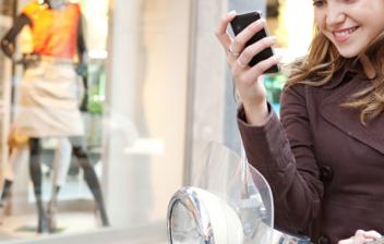 Mujer joven y sonriente con móvil en la mano junto a motocicleta.