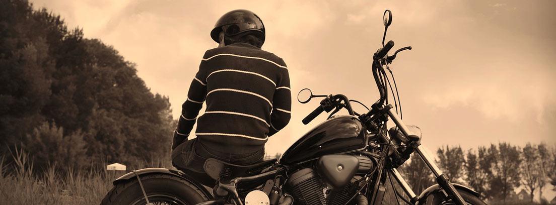 con casco sentado en moto parada en la carretera