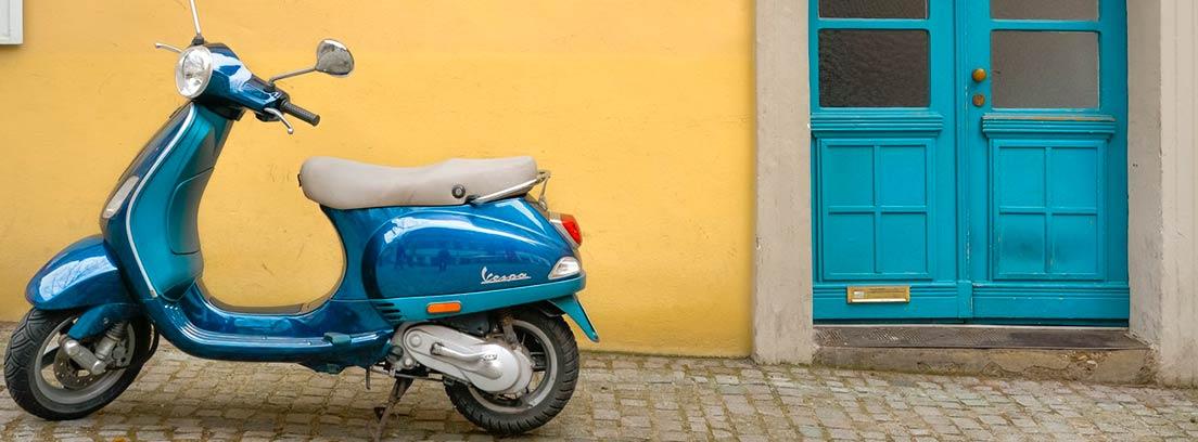 Moto azul aparcada junto a pared amarilla con puerta azul