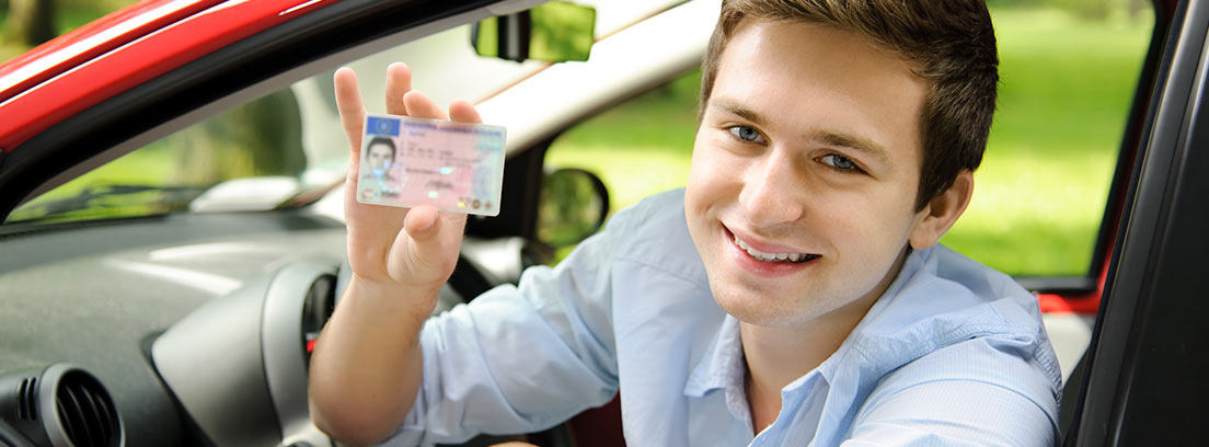 Hombre asomado a la ventanilla de un coche rojo sujetando un carnet de conducir