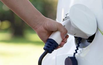 Mano colocando un cargador de coche eléctrico