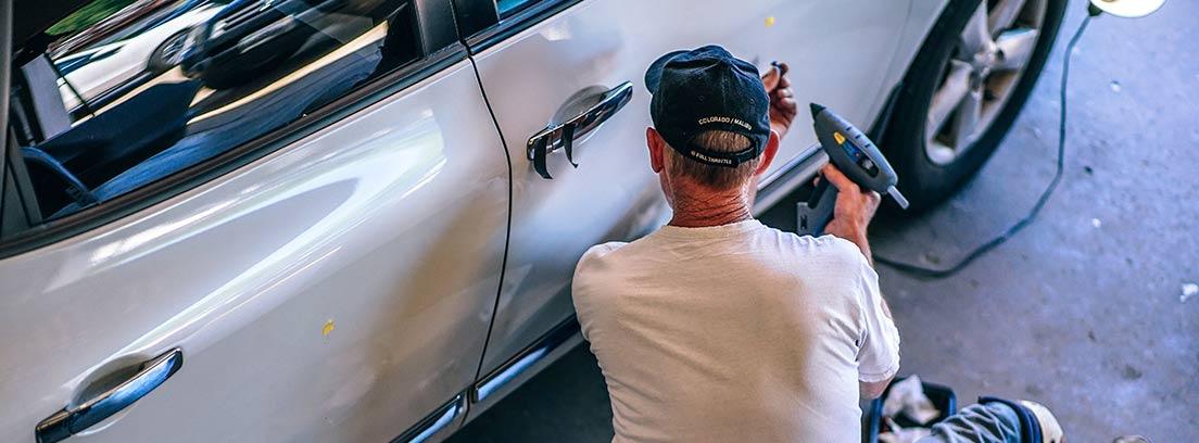 Hombre con herramienta y sentado delante de la puerta de un coche