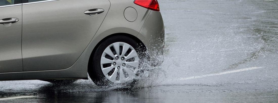 Parte de atrás de coche con rueda sobre agua