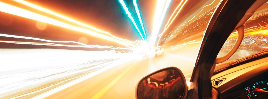 Vista lateral de coche dentro de un túnel con luces de neón.