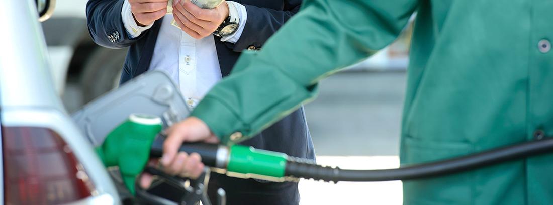 Hombre repostando gasolina en un coche junto a otro hombre que sujeta un fajo de billetes
