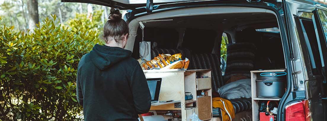 Persona de espaldas tecleando sobre portátil en la parte trasera de furgoneta campera