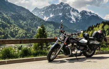 Moto apoyada en barrera de madera en carretera de montaña