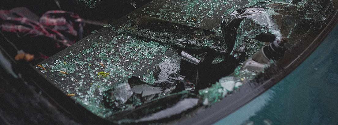 Luna delantera de coche rota y cristales dentro del vehículo