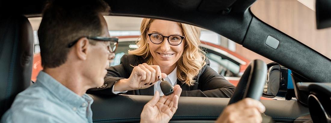 Hombre dentro de un coche y mujer fuera, asomada a la ventanilla con una llave en la mano