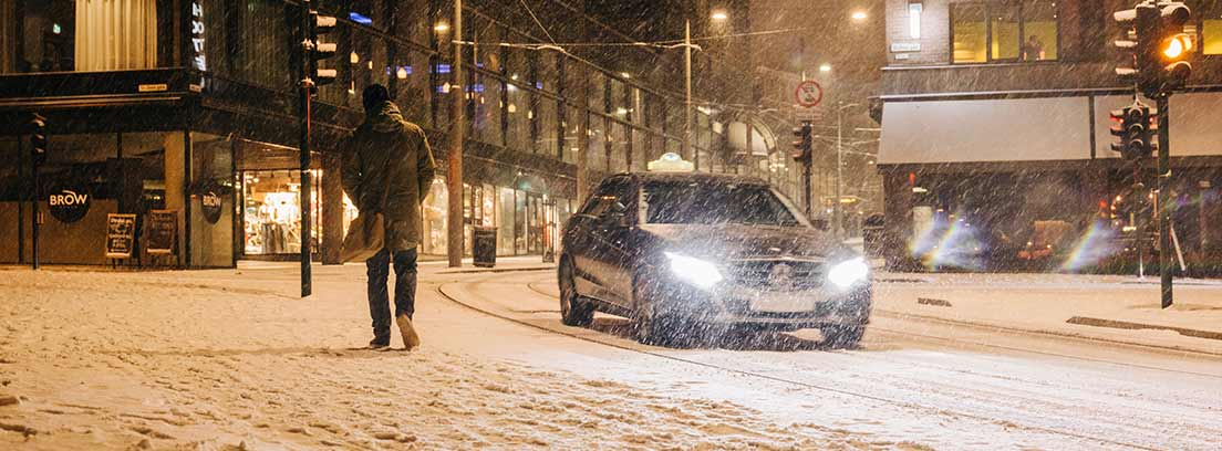 Coche con faros encendidos circulando de noche y sobre la nieve en una ciudad