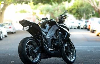 Vista trasera de moto aparcada en el medio de una calle.